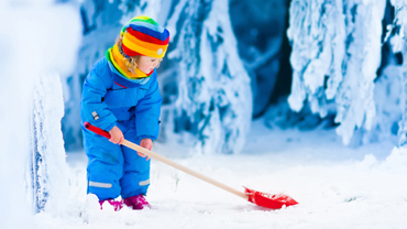 Kid shoveling snow to keep warm